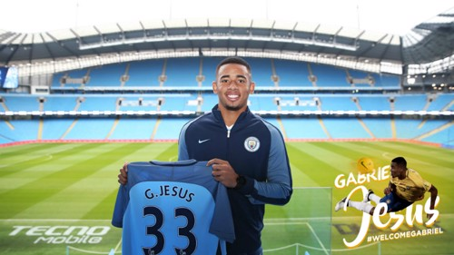 Gabriel Jesus holds up his City shirt with the Etihad Stadium pitch in the background