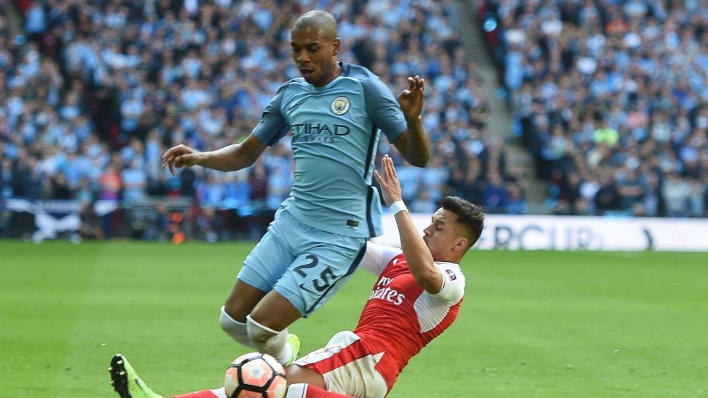 BOOKED: Sanchez receives a yellow for his foul on Fernandinho